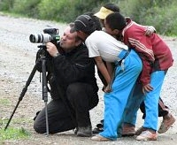 picture shows photographer and tourguide peter pap on a trip in tibet 2007 taking photos while tibetan children are watching
